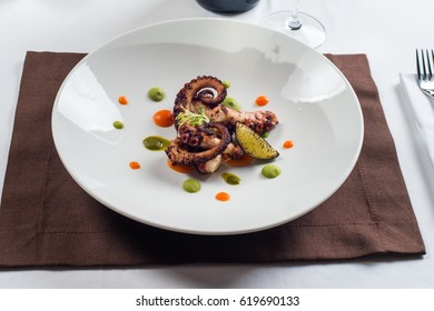 grilled octopus cut with a knife for food on a white plate