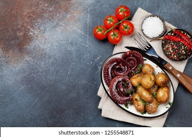 Grilled octopus with small potatoes with herbs and spices. Top view with space for your text