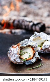 Grilled onion bulbs with herbs in foil