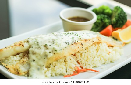 Grilled Pangasius Fillet with rice and topping with tartar sauce on white plate served with Vegetables