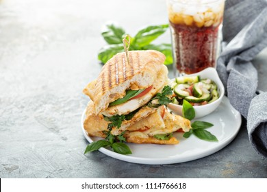 Grilled panini sandwich with chicken and cheese served with vegetable salad and soda