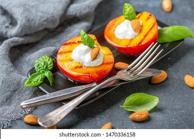 Grilled peaches with honey, yogurt, almonds and fresh basil in a black plate on a grey textured background, selective focus.