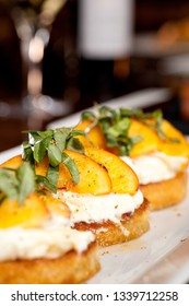 Grilled Peaches with Ricotta Cheese and Basil bruschetta on a white plate