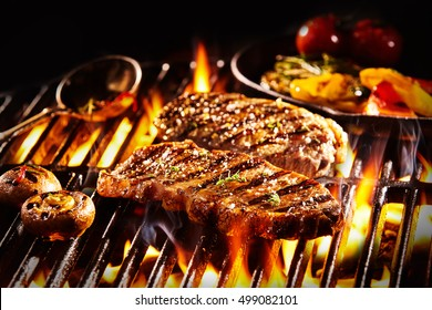 Grilled pieces of delicious rump steak garnished with herbs and sauce alongside mushrooms and vegetables over flames