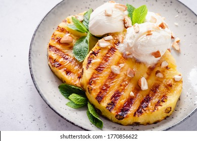Grilled pineapple with scoops of vanilla ice cream