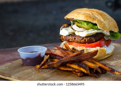 grilled plant based burger served with a home made sauce sweet potato fries on a wooden cutting board