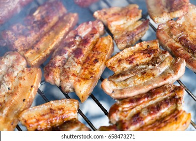 Grilled pork belly, bacon, on hot traditional charcoal bbq close up. Horizontal macro shot