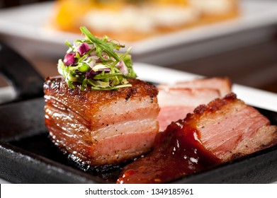 Grilled pork belly with coleslaw and spicy bbq sauce served on a hot skillet