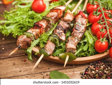 Grilled pork and chicken kebab with paprika in round wooden plate of lettuce salad, on wooden background with tomatoes and spinach.