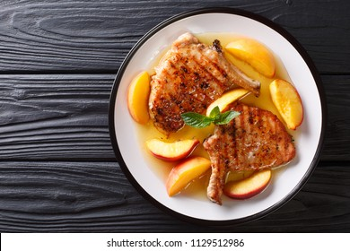 grilled pork chop with glazed peaches and honey garlic sauce close-up on a plate on a table. horizontal top view from above