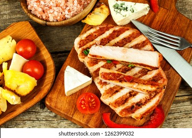 Grilled pork chop on a wooden board. Protein food. Grilled meat. Food preparation. Protein diet.