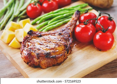 grilled pork chop serve with vegetable on wooden board for meal