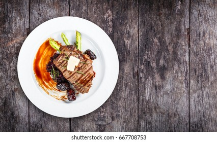 Grilled pork chop steak with dates in honey, rosemary, asparagus and beet salad on wooden background. Hot Meat Dishes. Top view, flat lay