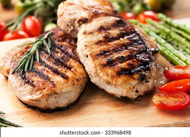 grilled pork chop with vegetable on wooden board