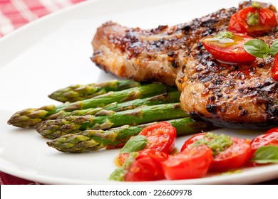 Grilled pork chops and asparagus. Served with fried grape tomatoes salad and pesto sauce.