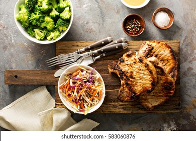 Grilled pork chops with cole slaw salad and steamed broccoli.