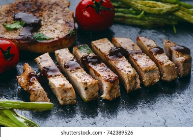 Grilled pork chops, steaks with vegetables, tomatoes, beans and sauce on a black slate. Fresh meat with foam. Dark background. Grilled and barbecue concept.