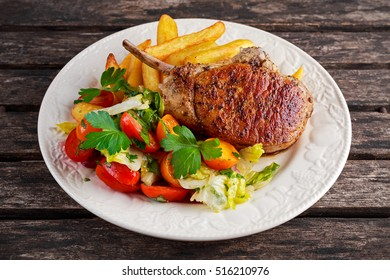 Grilled pork cutlet meat garnished with potato and salad on a wooden table.