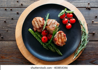 Grilled pork dish with fresh vegetables. Food photography of grilled pork medallions with herbs and spices. Tasty cook meat with  vegetables on dark wooden background.