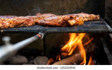 grilled pork with flames on charcoal barbecue