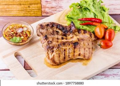 Grilled pork jowl favorite Thai street food on wooden background