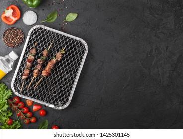 Grilled pork kebab with paprika on disposable coal bbq grill with fresh vegetables on blackbackground. Salt and pepper with lettuce and paprika and cherry tomatoes and spirit bottle.