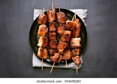 Grilled pork kebabs on dark background with copy space, top view.