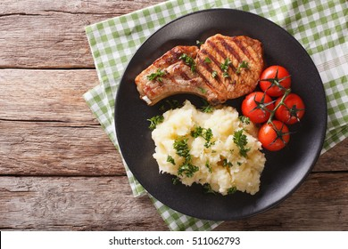 Grilled pork loin with mashed potatoes and tomato close-up on a plate. Horizontal view from above