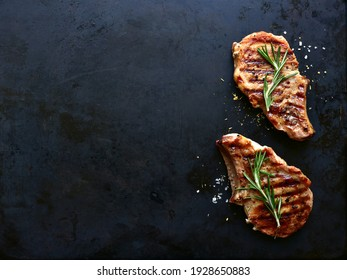 Grilled pork loin on a bone on a black metal background. Top view with copy space.