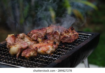 Grilled pork meat on the small grill.