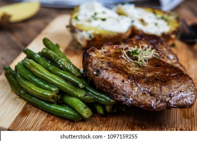 Grilled pork neck steak and green beans and baked potatoes
