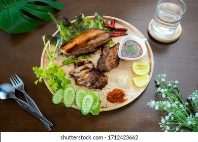 Grilled pork on a wooden tray with   side dishes and ingredients (Top view)
