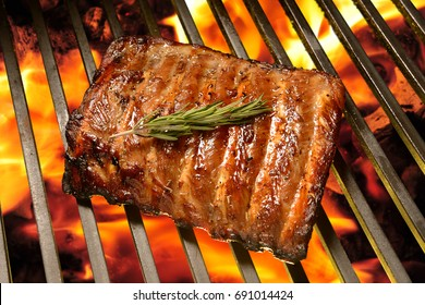 Grilled pork ribs on the flaming grill