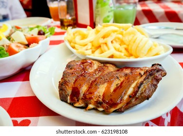 Grilled pork ribs on white plate with french fries, salad on lunch table set