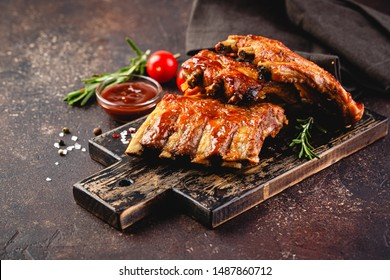 Grilled pork ribs on a wooden cutting board on a brown background