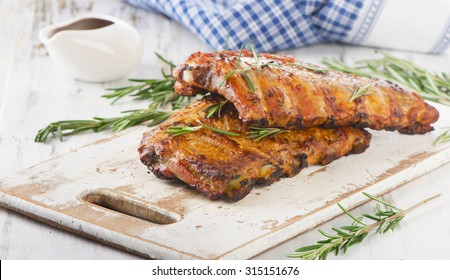 Grilled pork ribs  on a wooden cutting board. Selective focus