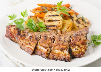 Grilled Pork Ribs and Potatoes on a Plate. Selective Focus