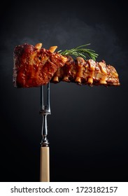 Grilled pork ribs with rosemary on a fork. Black background.