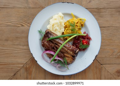 Grilled pork ribs with sauerkraut and mash potatoes on restaurant table