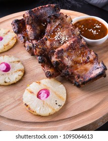 Grilled pork ribs served with pineapple on a board