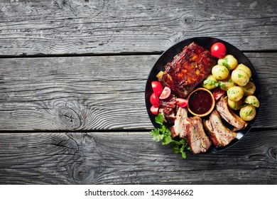 grilled pork ribs topped with barbecue sauce served with tomato salad and boiled hot new potatoes served on a black plate on a rustic wooden table, view from above, empty space, flat lay