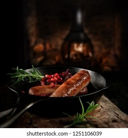 Grilled pork sausages with caramalized red onions and pomegranites in a wrought-iron black skillet shot against a dark background with accommodation for copy space.