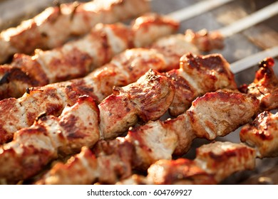 Grilled pork shashlik kebabs On Barbecue outdoors at back yard. Meat lamb kebab on BBQ. Barbecue shish kebab at outdoor picnic - top view, selective focus, series.