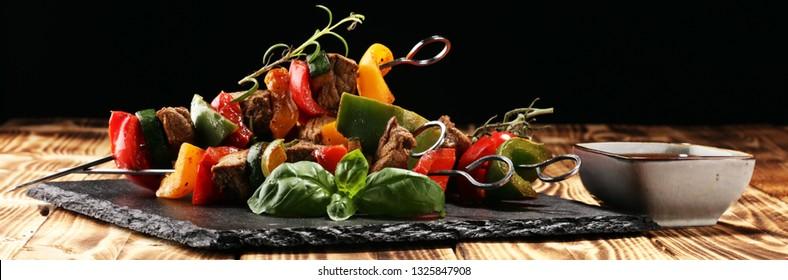 Grilled pork shish or kebab on skewers with vegetables . Food background shashlik or chicken skewers