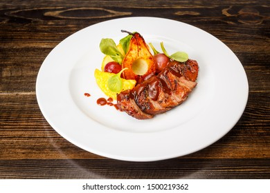 Grilled pork steak with caramel pear, orange and grape served on white pate