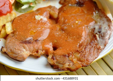 grilled pork steak dressing gravy and french fried on plate