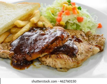 Grilled pork steak fillet with black pepper sauce, vegetable salad,  bread and french fries on white plate