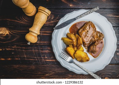 Grilled pork steak and fried potatoes on white plate on dark wood table