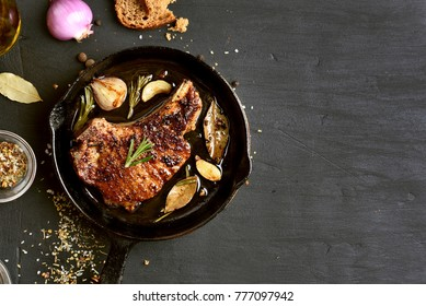 Grilled pork steak in frying pan on black background with copy space. Top view, flat lay food