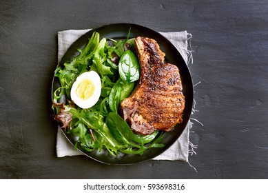 Grilled pork steak with green salad in plate on dark background, top view